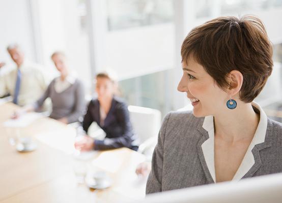 Durch Outplacementberatung zufriedene Frau im Konferenzraum